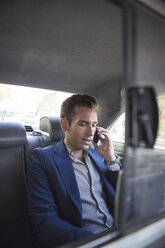 Businessman talking on phone while traveling in car - CAVF03078
