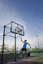 Man dunking ball in hoop at park against sky - CAVF03129