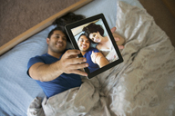 Overhead view of happy couple taking selfie through tablet while lying on bed - CAVF03186