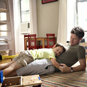 Smiling son lying on father at home - CAVF03222