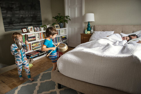 Children playing with utensils while parents lying on bed at home - CAVF03231