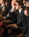 Man using opera glasses in theater audience - CAIF08130