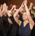 Enthusiastic women clapping in theater audience - CAIF08133