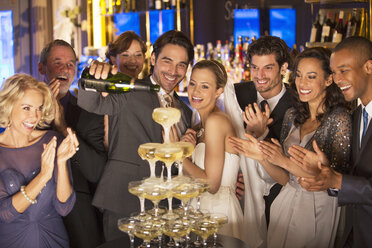 Bride and group pouring champagne pyramid at wedding reception - CAIF08136
