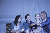 Man pouring champagne for friends - CAIF08139