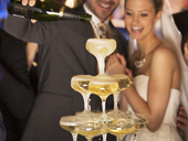 Groom pouring champagne pyramid at wedding reception - CAIF08151