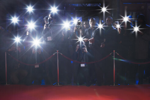 Paparazzi using flash photography behind rope on red carpet - CAIF08154