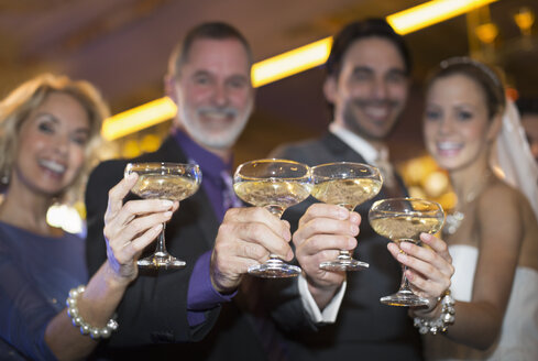 Portrait of bride and groom toasting champagne with parents - CAIF08157