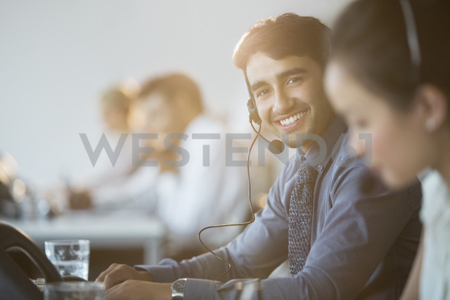 Businessman wearing headset in office - CAIF08169