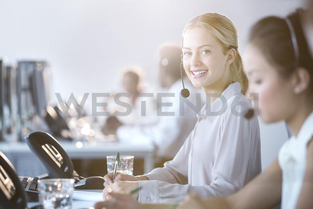Businesswoman wearing headset in office - CAIF08172