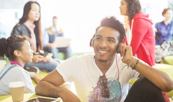 University student listening to headphones in lounge - CAIF08205