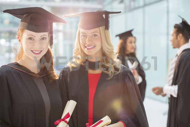 Smiling graduates holding diplomas - CAIF08211
