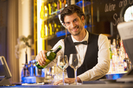 Portrait of well dressed bartender pouring wine in luxury bar - CAIF08247