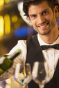 Close up portrait of well dressed bartender pouring wine - CAIF08253