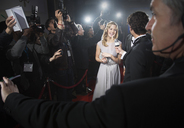 View over bodyguard's shoulder of celebrity being interviewed on red carpet - CAIF08256