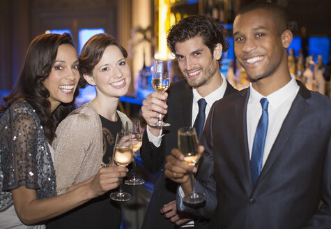 Portrait of well dressed couples toasting champagne flutes - CAIF08277