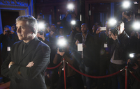 Paparazzi using flash photography behind bodyguard at red carpet event - CAIF08280