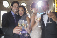 Portrait of well dressed couples toasting champagne and wine glasses - CAIF08298