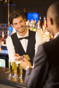 Well dressed bartender taking credit card from customer in luxury bar - CAIF08328