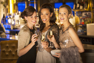 Portrait of well dressed women smiling with champagne flutes in luxury nightclub - CAIF08334