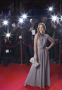 Portrait of well dressed female celebrity on red carpet with paparazzi in background - CAIF08343