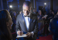 Well dressed celebrity signing autograph on red carpet - CAIF08367