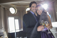 Portrait of well dressed couple toasting wine and champagne glasses - CAIF08382