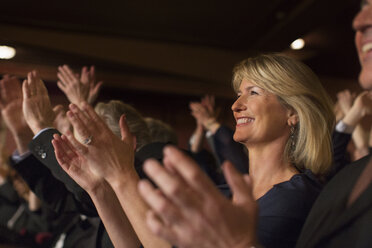 Close up of enthusiastic woman clapping in theater audience - CAIF08388