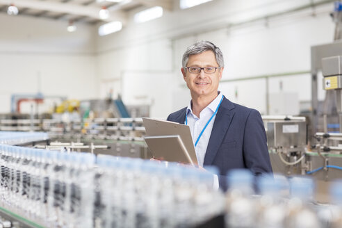 Supervisor smiling in bottling plant - CAIF08415