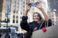 Woman taking selfie while standing against buildings in city - CAVF03538