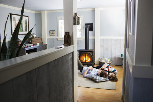 Couple relaxing on floor in living room at home - CAVF03589