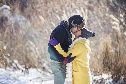 Side view of couple kissing while standing on snow covered field - CAVF03604