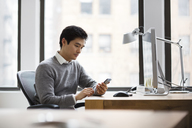 Man using smart phone while working in office - CAVF03613