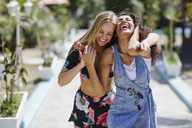 Two laughing young women outdoors in summer - JSMF00110