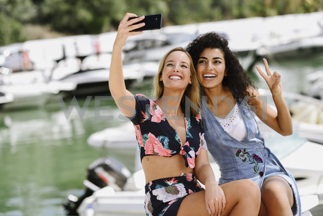 Two happy young women taking a selfie at marina in summer - JSMF00113