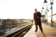 Businessman waiting for train at subway station against clear sky - CAVF03659
