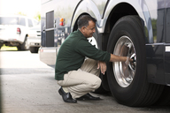 Man examining bus tire at workshop - CAVF03737