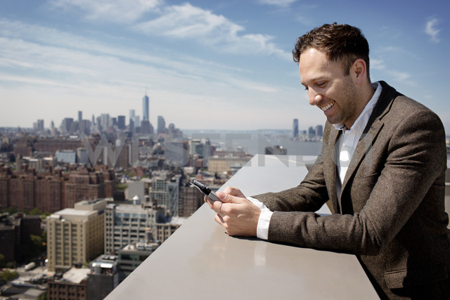 Happy businessman using tablet computer on building terrace - CAVF03770