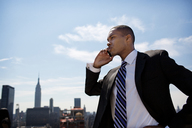 Low angle view of businessman using mobile phone against sky - CAVF03773