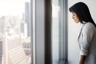 Businesswoman looking through window in office - CAVF03809