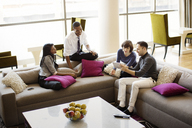 High angle view of colleagues talking while sitting on sofa in office - CAVF03827