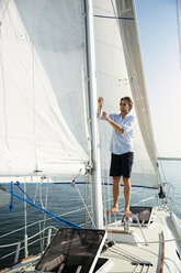 Man adjusting rope while standing on yacht - CAVF03914