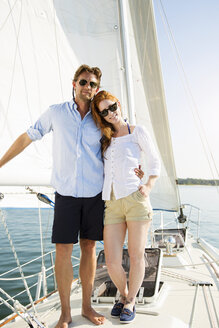 Portrait of happy couple standing at yacht - CAVF03917