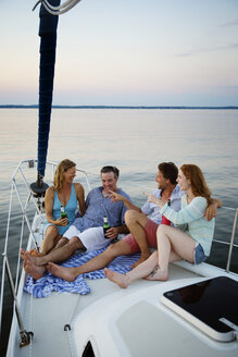 Happy couples enjoying drink while traveling in yacht - CAVF03953