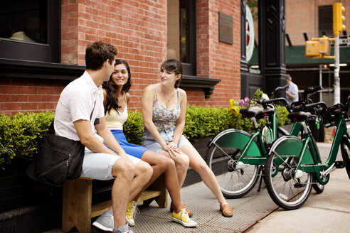 Friends with bicycle talking while sitting on bench at sidewalk cafe - CAVF03971