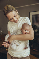 Newborn baby being held in mother's arms - MFF04394