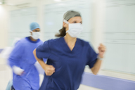 Doctors rushing through hospital corridor - CAIF08436