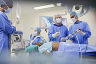 Team of surgeons operating on patient in hospital - CAIF08445