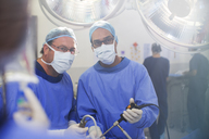 Portrait of doctors performing laparoscopic surgery in operating theater - CAIF08454