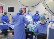 Team of doctors performing surgery in operating theater - CAIF08463